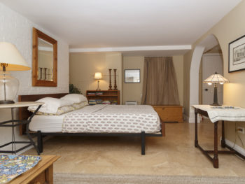 Well-furnished bedroom filled with a platform bed, bedstand, side table, three lamps, bookshelf, & large mirror
