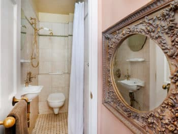 Cream-tiled bathroom with a white toilet, sink, curtains,& gold shower head & a gold framed mirror