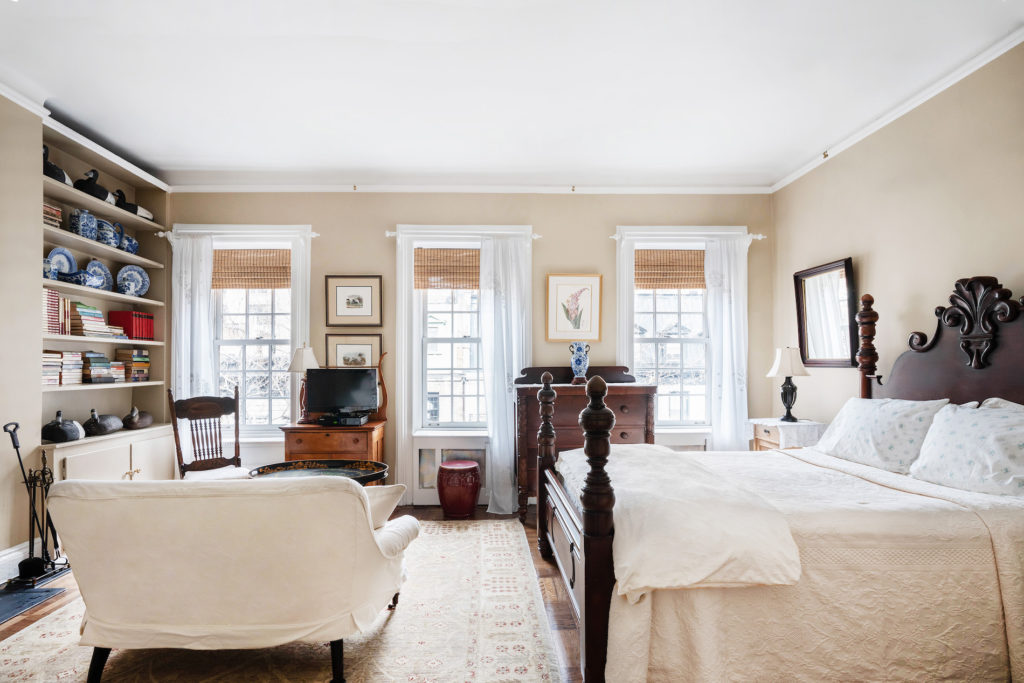 four poster bed with white bedspread and white loveseat