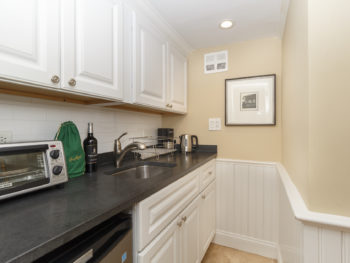 kitchenette with black absolute granite, white cabinets above and below, a print on the wall, wainscot on lower half of walls and one black and white print.