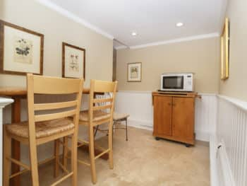 dining area with tall counter height table with two stools light colored wood. Two prints on walls. Cabinet with Microwave oven. Light colored yellowish walls and light beige stone floors. Wainscot walls on lower part of walls.
