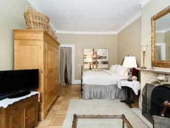 Large room with queen bed. Pine armoire. Light colored persian rug. Taupe walls. TV.