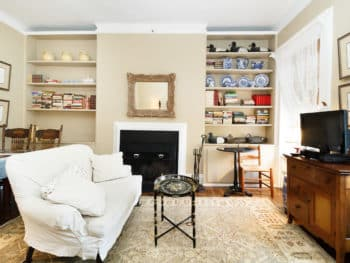 Large Livingroom with loveseat, black oval metal coffee table, beige oriental rug, beige walls, simple fireplace with gold framed mirror above