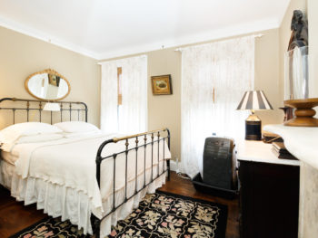 Large Back Bedroom Beige Walls, Iron and Brass Queen Bed, Rug, antique dresser, mirror behind bed. Lamp and painting