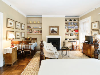 Large room with beige walls, table with light blue table cloth and chairs in corner, many prints of dogs on wall, gold framed mirror over fireplace, bookshelves with books and decoy ducks and miscellaneous things