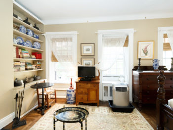 room with beige walls, bookshelf, coffee table, tv on small wood cabinet, two windows lace clad, light oriental rug.