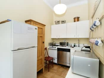 Kitchen showing white refrigerator and white cabinets. Antique pine hutch. Microwave. Stainless steel dishwasher.