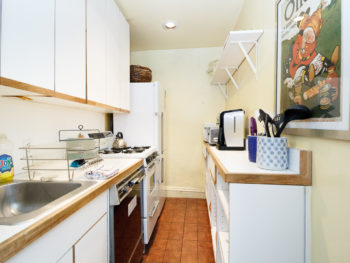 Kitchen with light yellow walls, white cabients and light brown floor.