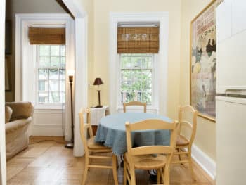 Dining Room area with window. Blue table cloth and 4 chairs. Wood Floors.