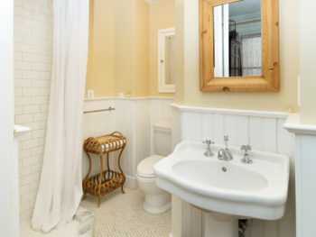 Bathroom with light yellow walls and white pedestal sink and shower with white curtains