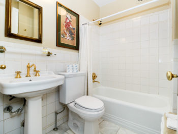 Bathroom with white square tiles, white pedestal sink and toilet. Brass faucet. Prints on walls.