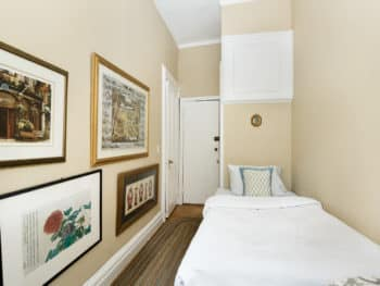 small bedroom with twin bed, no headboard, taupe paint color, long braided rug, 4 prints on the wall