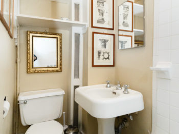 bathroom with light beige walls, white pedestal sink, toilet. Mirror above toilet and sink. two prints. Shelves.