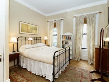 Eggshell-painted bedroom furnished with a large cream bed, two curtained windows, two bedstands, & a bookshelf