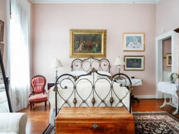 A well-lit bedroom with pastel pink walls, off-white bedding, dark decorative rug, Queen antique iron bed frame, large print on bed wall, and lace clad windows.
