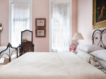 iron bed with scrolling, white bedding, pink walls, full length mirror on stand