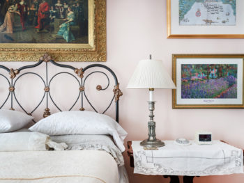 Room with pink walls, iron bed with scrolling, bedside table with white table cloth and silver lamp, prints on walls