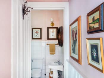 Bathroom with white tiling, pedestal sink and toilet
