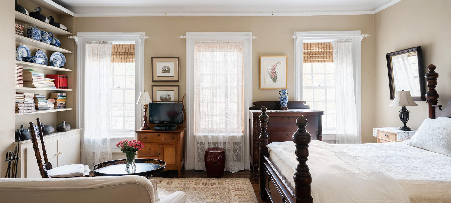 Large room with 3 large windows, four poster bed with wihite bed spread