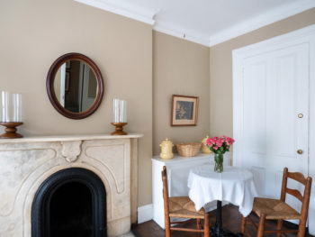 Wall with carved marble fireplace. Small round table with flowers.