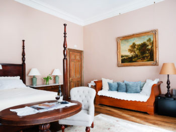 Bedroom with light pink walls. Daybed with blue pillows. Four poster bed. Area rugs on floor.