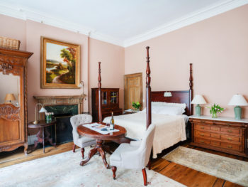 Bedroom with pale pink walls. Four poster bed and oval table at foot of bed. Area rugs on floor.