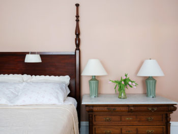 Corner of four poster bed with white bedspread and white pillows. Marble topped dresser with two green lamps.