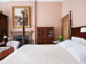 Spacious bedroom with pink walls. Four poster bed with white bedspread. Large Painting above fireplace.