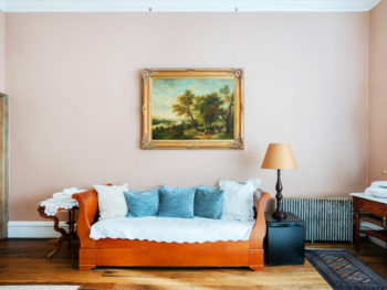 Large bedroom with pink walls. Daybed with white bedspread and blue pillows.