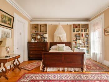 Dark Wood Sleigh Bed with mosquito netting, dark wood dresser next to bed, red oriental rug, beige walls