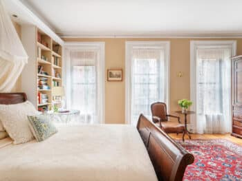 Room with beige walls, 3 windows with lace curtains and bed with white coverlet. Red Rugs.