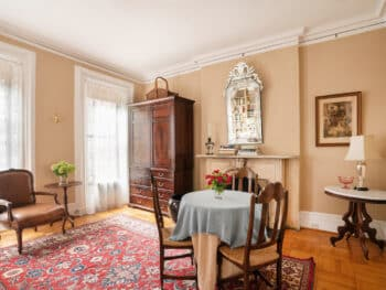 Room with Beige walls, brown wood armoire and table with blue table cloth and 3 chairs. Red Rugs and Mirror above fireplace