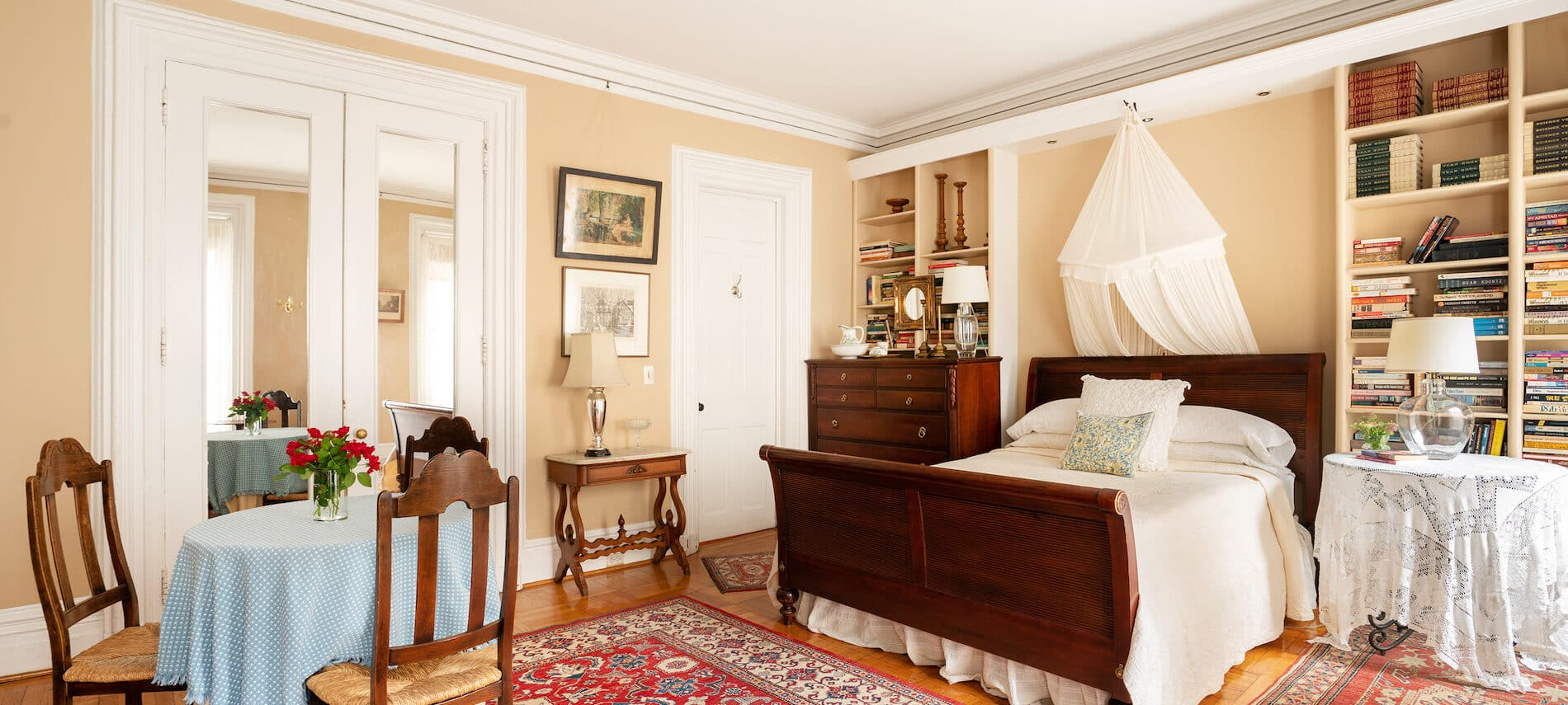 Bedroom with beige walls. Dark wood sleigh bed. White coverlet and mosquito netting.