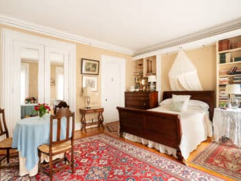 Room with beige walls, red carpets and bed with white coverlet
