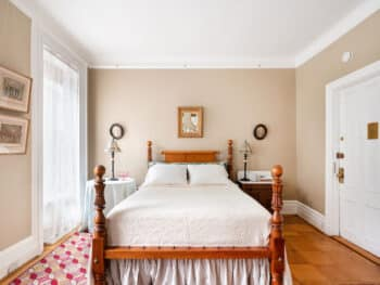 four poster bed with white cover. Red rug. Beige walls.