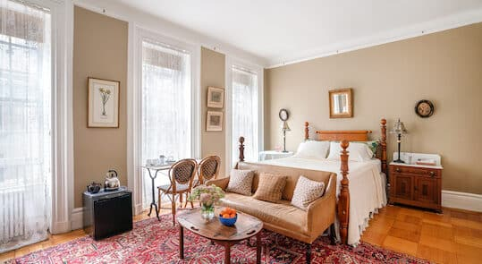Bedroom with four poster bed, ivory bedding, area rug and 3 windows