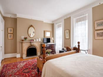 four poster bed with white cover. Red rug. Beige walls. Fireplace with mirror above.