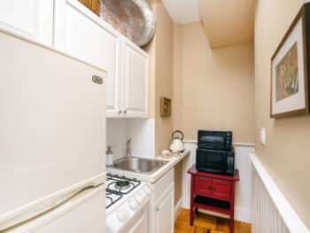 Small kitchen with beige walls, black microwave, red table