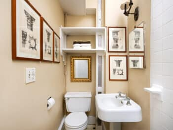 Bathroom with many prints. White pedestal sink