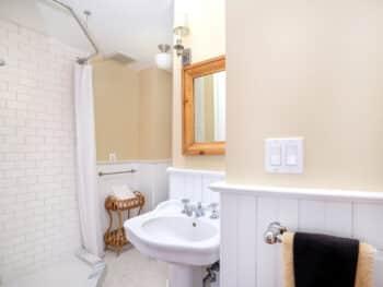 bathroom with white pedestal sink and beige walls.