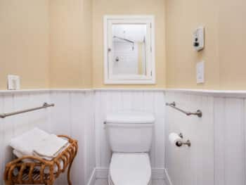 bathroom with beige upper walls and white wood walls on bottom. Toilet and mirror above.