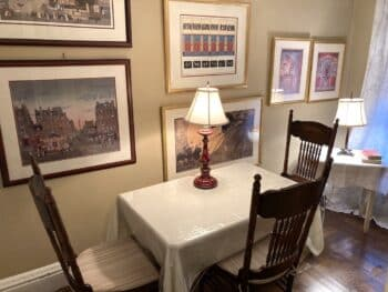 small room with table and chairs and prints on the wall