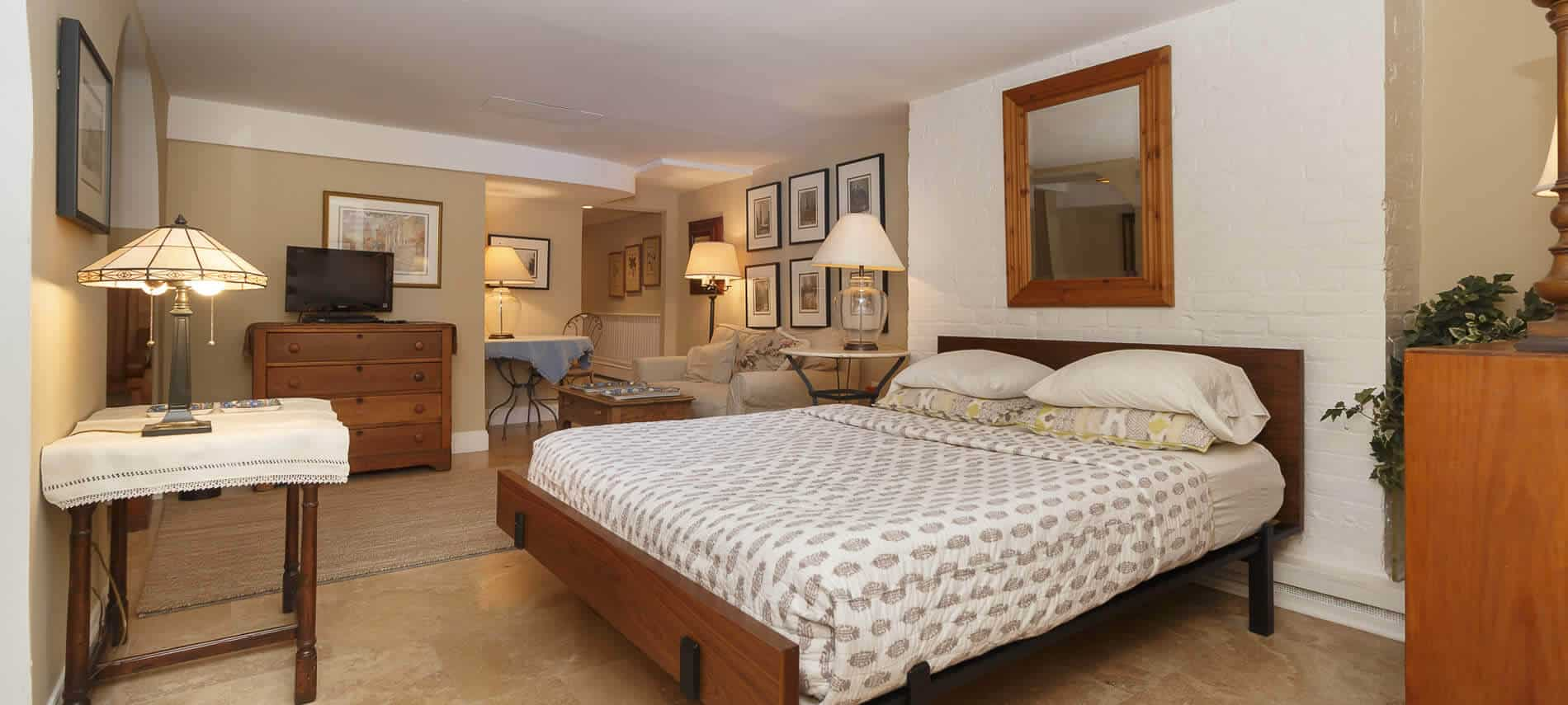 A large beige & cream bedroom filled with a king platform bed, wooden dresser & tv, & side tables with lamps