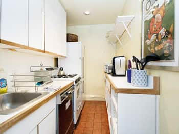A bright eggshell-painted kitchen area with white appliances, cabinets, & shelf with a black dishwasher