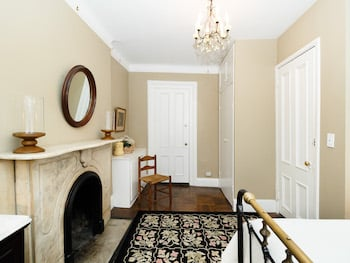 Bedroom with Marble Fireplace, Mirror over fireplace, rug & Chandelier. Beige Walls.