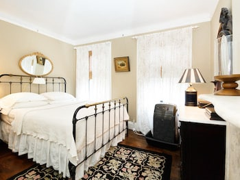 Larger Back Bedroom Beige Walls, Iron and Brass Queen Bed, Rug, antique dresser, mirror behind bed. Lamp and painting