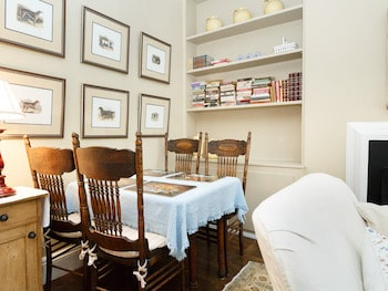 Dining Table with Table Cloth and 4 antique oak chairs. six prints of dogs on the wall. Book Shelf with books and small objects.