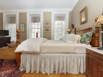 Side view of a beige-decorated bedroom with a wooden poster bed, three tall windows, & two bedstands
