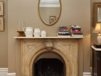 Marble Fireplace with oval mirror above. Taupe Walls.