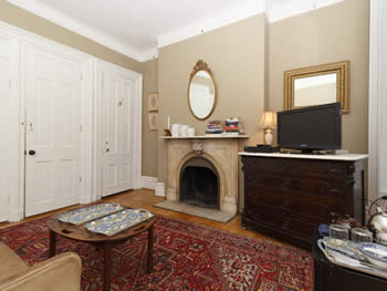 Taupe walls sitting area with a large dark wood dresser with marble top, a tv, & mirror over fireplace & a small coffee table & red rug
